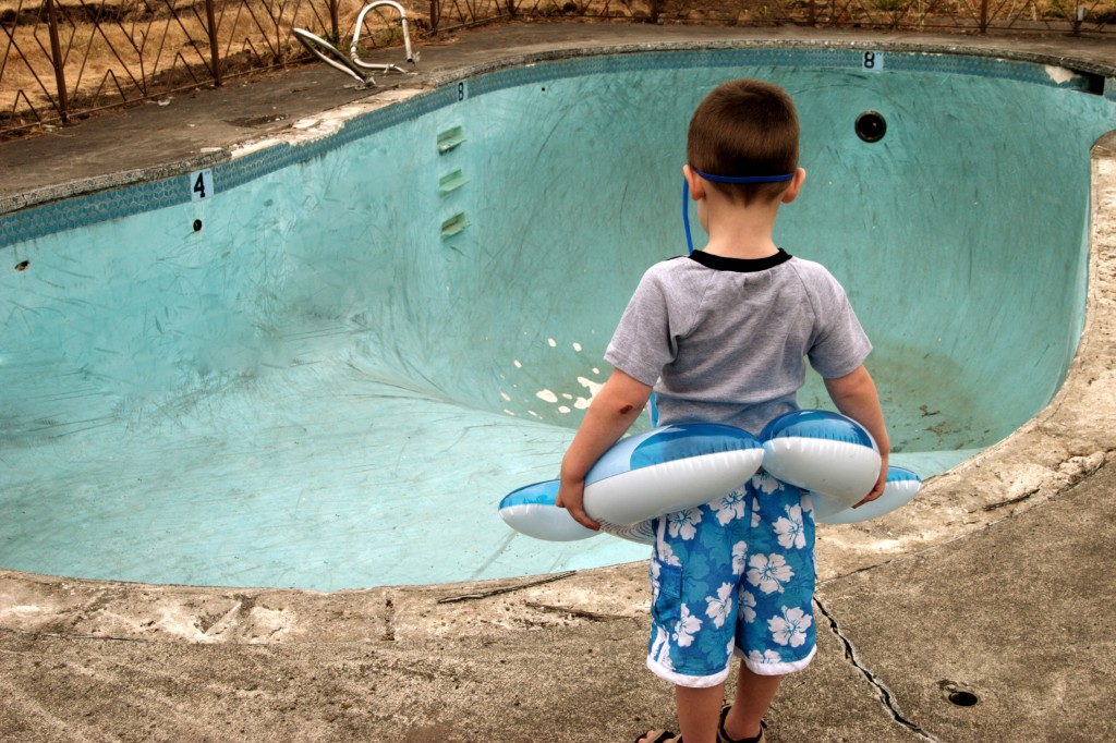 Small boy wearing a floaty and goggles stares at an empty swimming pool.